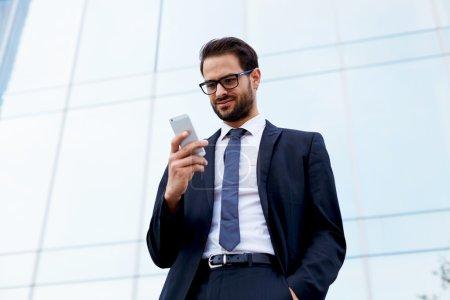 Photo pour Heureux homme d'affaires souriant en lisant un message texte debout devant le bureau - image libre de droit