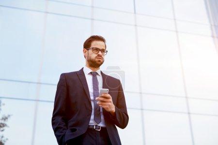 Photo pour Bel homme d'affaires recevant des nouvelles choquantes lorsqu'il lit un message texte sur téléphone mobile - image libre de droit