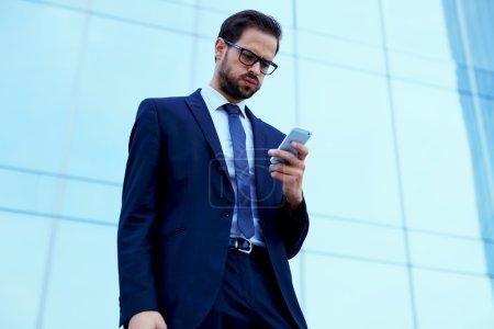 Photo pour Les employés mécontents lire SMS sur téléphone portable debout contre l'immeuble de bureaux de gratte-ciel - image libre de droit