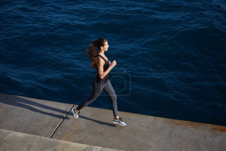 young woman running along the cement pier