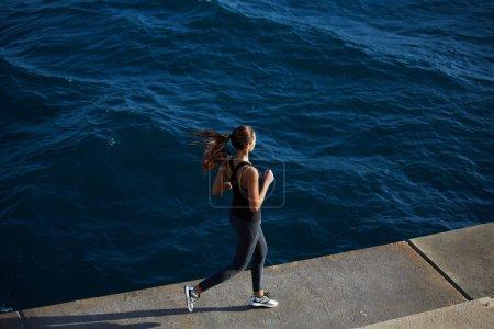 female runner jogging next to the ocean