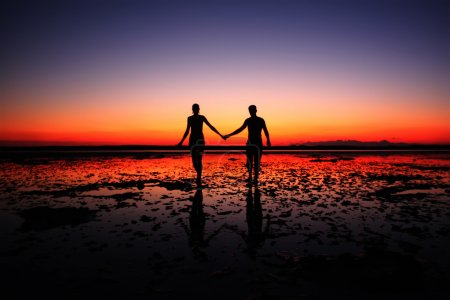 Couple walking hand in hand on sunset