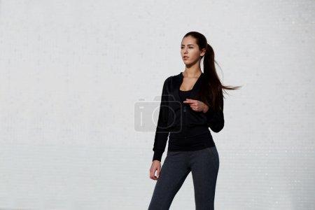 Woman dressed in sportswear posing