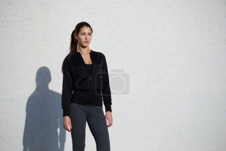 Woman dressed in sportswear posing outdoors