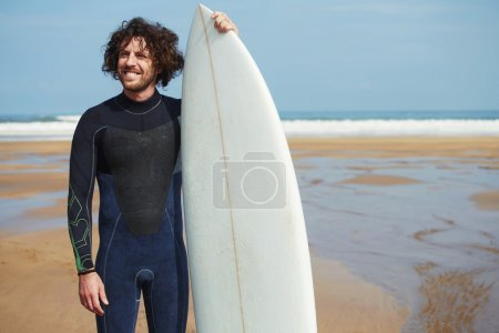Man with long hair holding surf board
