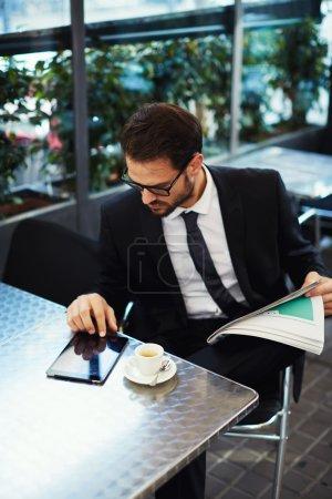 Photo pour Verticale d'un jeune homme d'affaires réussi s'asseyant dans un café et utilisant une tablette numérique, homme d'affaires ayant le petit déjeuner s'asseyant sur la belle terrasse avec des usines - image libre de droit