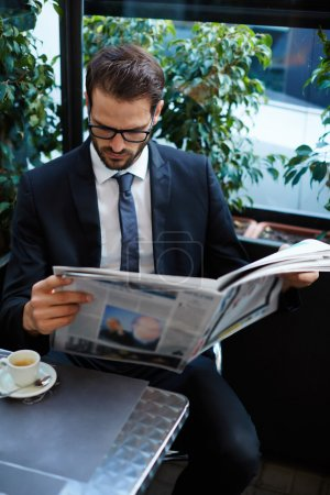 Photo for Portrait of young brunette hair businessman sitting in a coffee shop reading a newspaper looking concentrated, handsome business man holding open newspaper sitting in cafe - Royalty Free Image