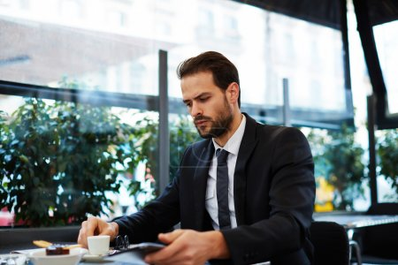 Photo pour Verticale d'homme d'affaires ayant le petit déjeuner s'asseyant sur la belle terrasse avec des usines, bel homme bien habillé dans le procès utilisant la tablette numérique pour le travail s'asseyant dans le café - image libre de droit