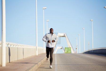 Man dressed in white windbreaker running