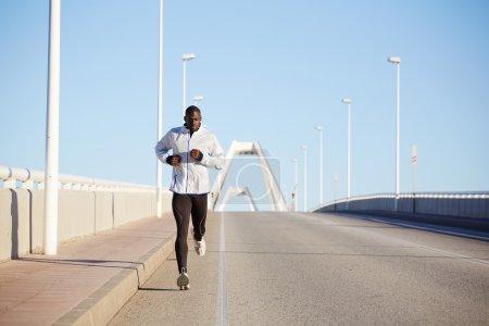Photo pour Beau sportif en forme vêtu d'un coupe-vent blanc qui court vite sur une belle route asphaltée par une journée ensoleillée - image libre de droit