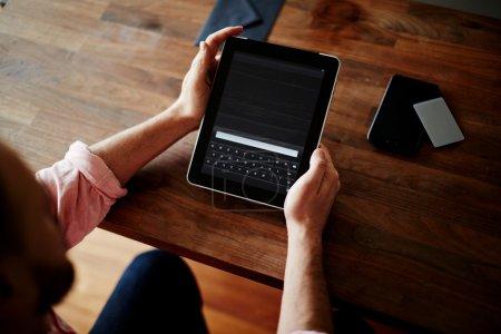 Photo pour Coupé des mains d'un homme à l'aide d'une tablette numérique au bureau de vannage, achats en ligne à la maison, processus croisé, image filtrée, sécurité des données - image libre de droit