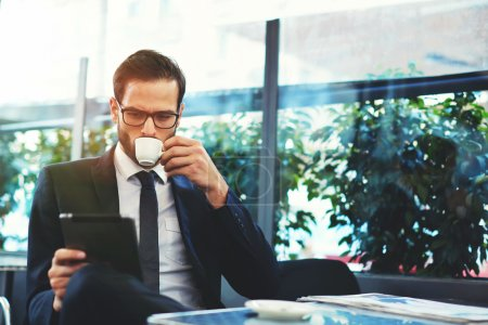 Photo for Portrait of handsome successful man drink coffee and look to the digital tablet screen sitting in coffee shop, business man having breakfast sitting on beautiful terrace with plants - Royalty Free Image