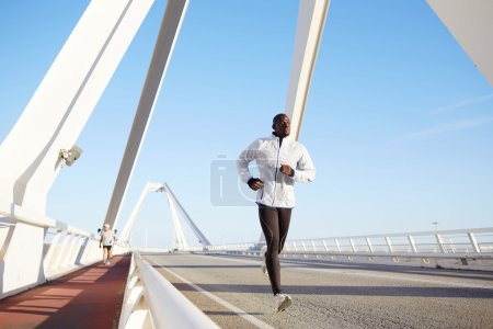 Athletic male running on a bridge