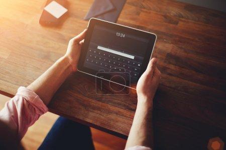 Man's hands using a digital tablet
