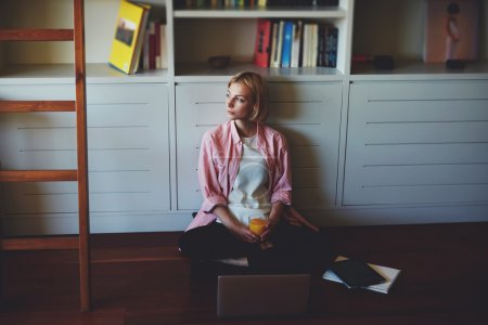 Woman sitting at bookshelf