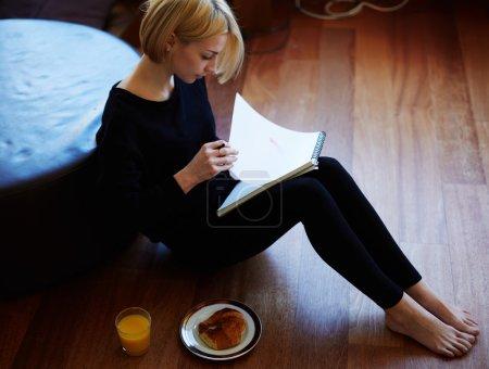 Photo pour Belle jeune femme écrivant quelque chose dans le bloc-notes tout en étant assise sur le sol au salon, charmante femme étudiant faire des devoirs à la maison, fille écrit un journal intime à son petit déjeuner, lumière vive - image libre de droit