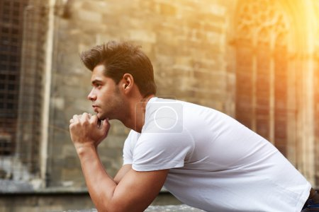 Photo for Side shot portrait of handsome man resting chin on clasped hands, confident man thinking about his choice, pensive man standing against gothic building, flare sun light, filtered image - Royalty Free Image