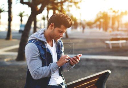 Photo pour Portrait d'un beau jeune homme envoyant un message texte tout en étant debout à l'extérieur, étudiant masculin lisant des messages texte à l'extérieur, élégant hipster brune utilisant un téléphone portable lors d'une soirée ensoleillée, soleil torride - image libre de droit