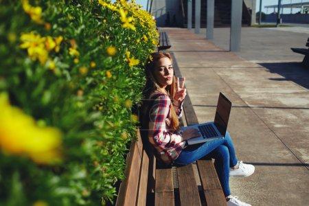 Photo pour Jeune fille d'étudiant de vue de côté s'asseyant devant un ordinateur portatif à l'extérieur et appréciant le jour ensoleillé sur le campus, femme charmante utilisant l'ordinateur tout en s'asseyant sur le banc en bois - image libre de droit