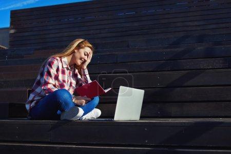 Photo pour Portrait d'une belle femme souriant à l'extérieur tout en utilisant son ordinateur portable, étudiant caucasien étudiant avec livre et ordinateur portable sur le campus, charmante étudiante souriant et s'amusant - image libre de droit