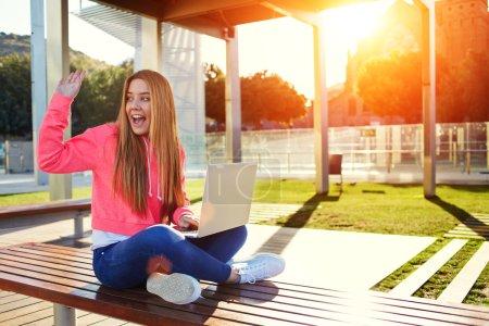 Photo pour Joyeux cheveux blonds étudiante femme saluant quelqu'un assis sur le banc du campus lors d'une belle journée ensoleillée, heureuse adolescente saluant bonjour tout en étant assise avec un ordinateur portable ouvert à l'extérieur, soleil éclatant - image libre de droit