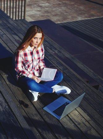 Photo pour Un cliché d'un étudiant caucasien étudiant avec un livre et un ordinateur portable sur le campus, une jeune femme attrayante utilisant un ordinateur portable assis sur un escalier en bois profitant d'une journée ensoleillée en plein air, une pigiste - image libre de droit