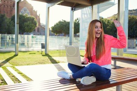 Photo pour Portrait de poils blonds joyeux femme étudiante saluant quelqu'un assis sur le banc du campus lors d'une belle journée ensoleillée, heureuse adolescente saluant bonjour tout en étant assise avec un ordinateur portable ouvert à l'extérieur - image libre de droit