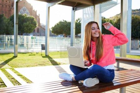Photo pour Superbe étudiante blonde saluant quelqu'un assis sur le banc du campus lors d'une belle journée ensoleillée, heureuse adolescente saluant bonjour tout en étant assise avec un ordinateur portable ouvert à l'extérieur - image libre de droit