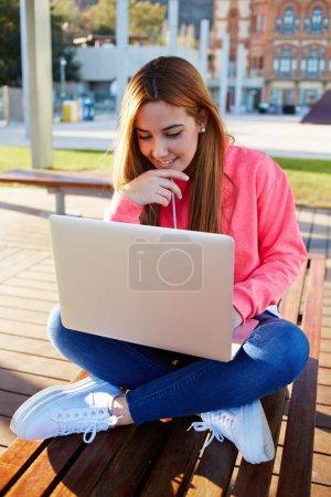 Photo pour Portrait de magnifique étudiante assise avec ordinateur portable ouvert sur le banc du campus contre le bâtiment de l'université, jolie adolescente à la recherche d'un écran de netbook avec sourire se sentant bien et heureux - image libre de droit