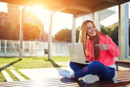 Photo pour Charmante étudiante blonde pointant vers un ordinateur portable ouvert tout en cherchant quelqu'un sur le campus, adolescente heureuse s'amusant tout en étant assise sur le banc avec un ordinateur ouvert à l'extérieur, soleil éclatant - image libre de droit