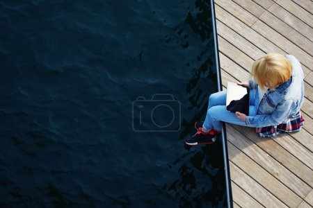 Photo for Top view shot of a young blonde hair woman sitting on a jetty next to a sea while using busy digital tablet with a blank screen, tourist woman searching information on tablet while relaxing on a pier - Royalty Free Image
