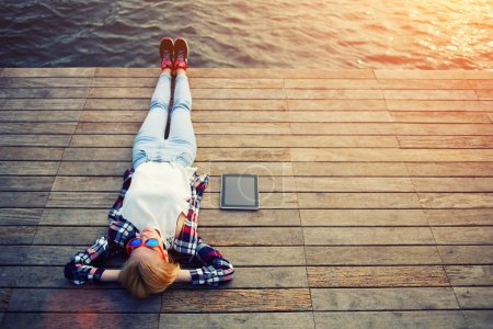Photo for Top view young woman lying on a wooden jetty enjoying the sunshine,tourist girl in bright summer glasses lying on jetty by river, vintage photo of relaxing young woman in nature with tablet, flare sun - Royalty Free Image