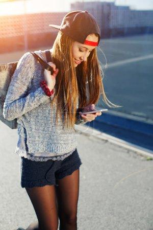 Foto de Bonita chica caminando al aire libre en la calle mientras usa ocupado un teléfono inteligente, hermosa joven con ropa de primavera casual caminando por una calle de la ciudad mientras envía mensajes de texto en su teléfono celular, sol de bengala - Imagen libre de derechos