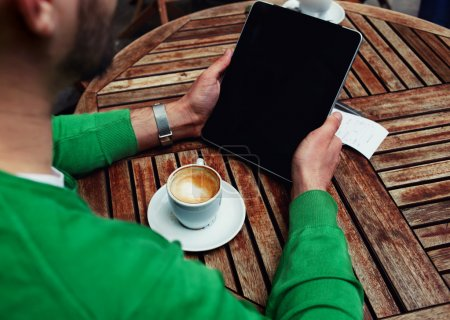 Photo for Rear view of male freelancer holding digital tablet with empty screen, man sitting at the table with cup of coffee while using touch screen tablet with blank screen, student working on tablet pc,flare - Royalty Free Image