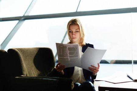 Photo pour Portrait de femme d'affaires attrayant lire les papiers ou documents assis dans la boutique de café de luxe près de la fenêtre, flou artistique, filtré image - image libre de droit