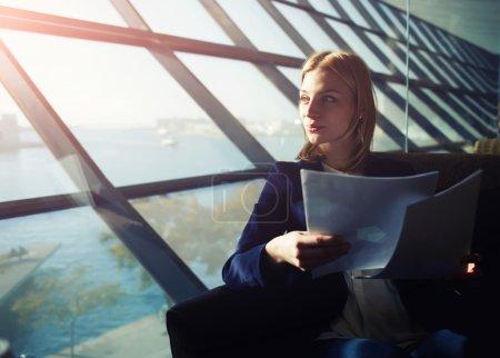 Photo pour Verticale de jeune femme élégante s'asseyant dans l'intérieur moderne de bureau retenant des papiers et regardant pensivemment hors de la fenêtre, image filtrée avec la lumière de soleil de fusée de la fenêtre - image libre de droit