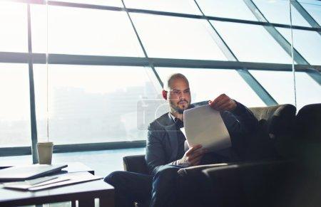 Photo pour Verticale de l'homme d'affaires beau examinant la paperasse dans l'intérieur de bureau, les documents ou les papiers masculins d'études exécutives pendant son temps de café - image libre de droit