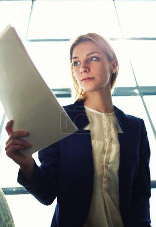 Photo pour Tir bas d'angle avec la jeune femme d'affaires attirante examinant la paperasse dans l'intérieur de bureau de lumière de bight s'asseyant à côté de la fenêtre, femme d'affaires a lu quelques documents avant la réunion, image filtrée - image libre de droit