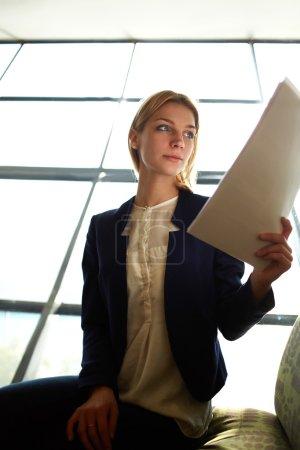 Photo pour Tir bas d'angle avec la jeune femme d'affaires blonde de cheveux examinant la paperasse dans l'intérieur de bureau de lumière de bight s'asseyant à côté de la fenêtre, femme d'affaires attirante a lu quelques documents avant la réunion - image libre de droit