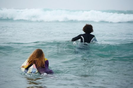 Two friends drifting on surfboards