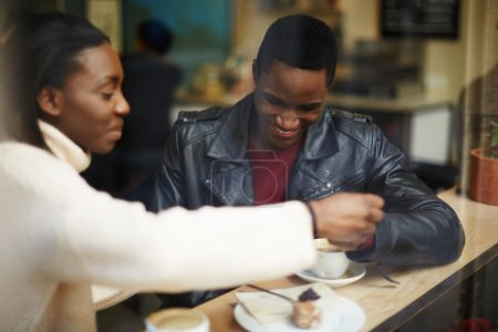 Dark skinned couple sitting in coffee shop
