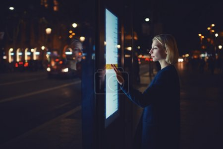 woman using modern application of bus stop