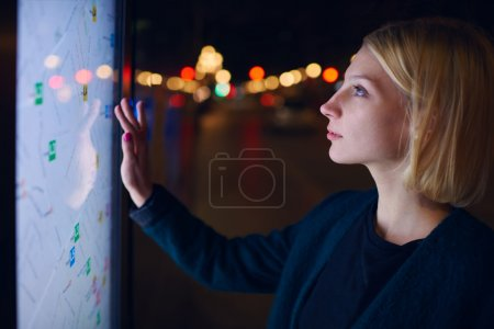 Photo for Gorgeous young woman standing front big digital screen with basic city street map GPS data, female touching sensitive display of modern smart city bus stop for check her location into the night - Royalty Free Image