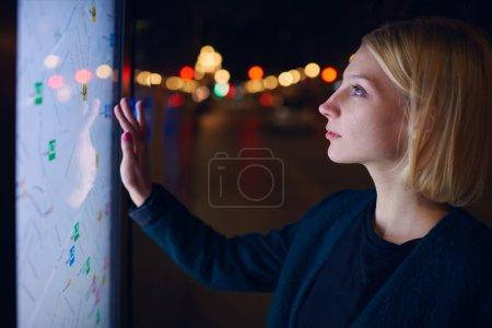 Photo pour Magnifique jeune femme debout devant grand écran numérique avec les données GPS de base de la carte de rue de la ville, affichage sensible touchant féminin de l'arrêt de bus moderne de ville intelligente pour vérifier son emplacement dans la nuit - image libre de droit