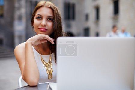 Photo pour Belle adolescente travaillant sur son ordinateur portable dans un bistro, jolie jeune femme assise à la table de café sur le trottoir avec netbook ouvert à côté d'elle, étudiante à l'université travaillant sur ordinateur dans un café - image libre de droit
