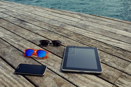 Photo pour Vue du dessus présentation maquette avec écran vierge tablette numérique, téléphone intelligent et quelques lunettes de soleil couché sur la texture en bois, vacances ou concept de temps de loisirs, objets sur jetée en bois - image libre de droit