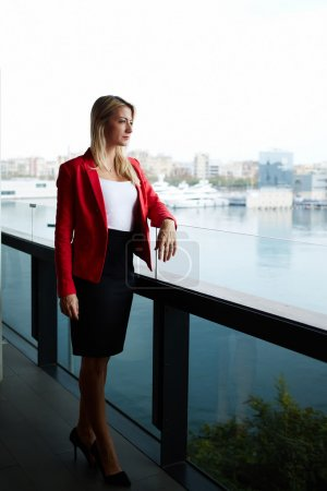 Photo for Elegant successful woman standing on the balcony of modern office building pensive looking away, rich well dressed woman standing in office exterior part with marina port view on background - Royalty Free Image