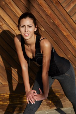 young female runner stretching