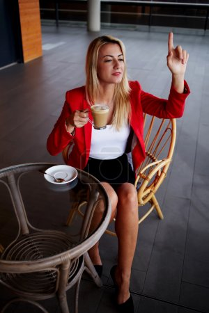 Photo for Elegant businesswoman calling for waiter while sitting at coffee shop, business lunch break of female executive, consumer asking for a bill at cafe - Royalty Free Image