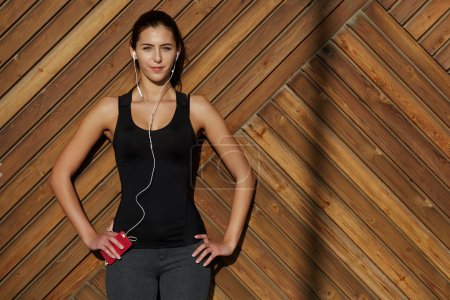 woman in sportswear listening music with headphones